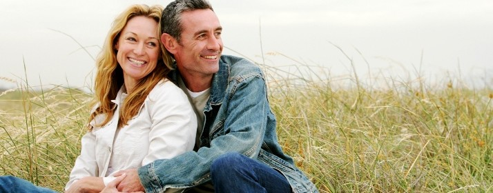 Couple sitting along grassy beachside